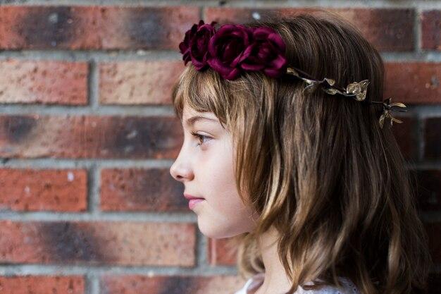 Ritratto di una bella bambina che indossa una corona di rose rosse sulla sua testa. stile di vita