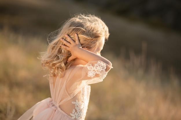 Ritratto di una bella bambina principessa in un abito rosa. in posa in un campo al tramonto
