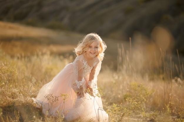 Ritratto di una bella bambina principessa in un abito rosa.