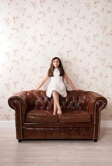 Ritratto di una bella bambina su un divano in pelle
