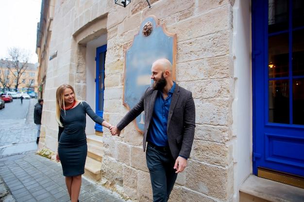 Ritratto di una bella coppia che cammina per strada in estate, ha una giacca elegante, vestita con un abito
