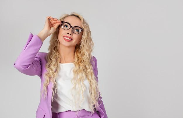 Ritratto di una bella donna abbastanza moderna con gli occhiali, gli occhiali toccanti, sorridendo amabilmente ed entusiasta,