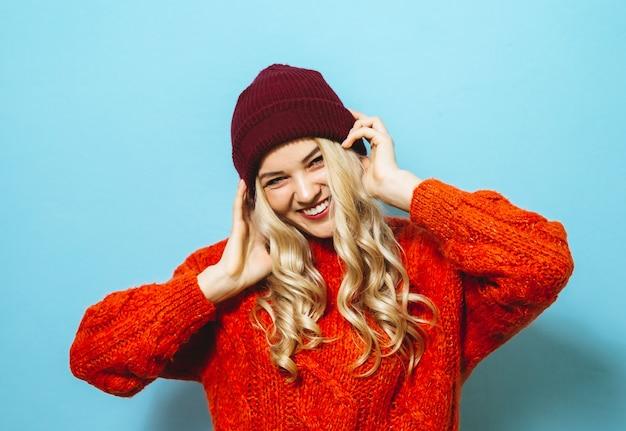 Ritratto di una bella donna bionda che indossa un cappello ed è vestito con un maglione rosso e mostrando la moda si sposta su sfondo blu