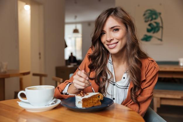 Ritratto di una bella donna che mangia un pezzo di torta