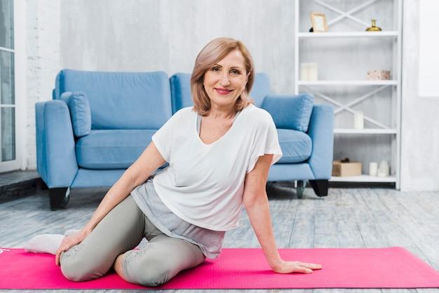 Ritratto di una bella donna felice che si siede sulla stuoia di yoga rosa che guarda l'obbiettivo