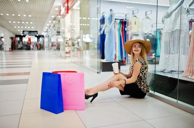 Ritratto di una bella donna in camicetta leopardata e gonna nera seduta sul pavimento a bere il caffè con le borse della spesa accanto a lei.