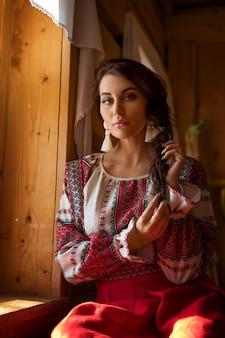 Ritratto di una bella donna in costume nazionale russo seduto alla finestra