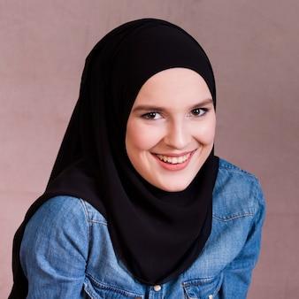 Ritratto di una bella donna musulmana sorridente su sfondo