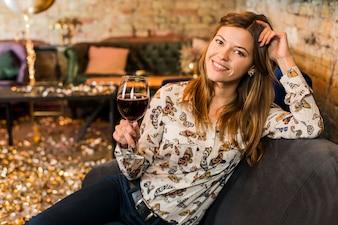 Ritratto di una bella donna sorridente con bicchiere di vino seduto sul divano