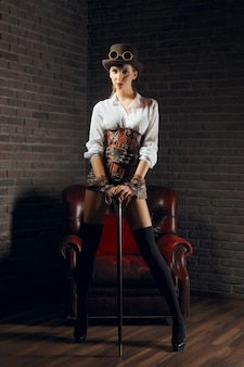 Ritratto di una bella donna steampunk in lingerie e calze, cappello e occhiali.