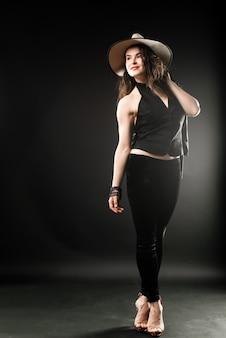 Ritratto di una bella donna su sfondo scuro con cappello da cowboy e giacca di pelle