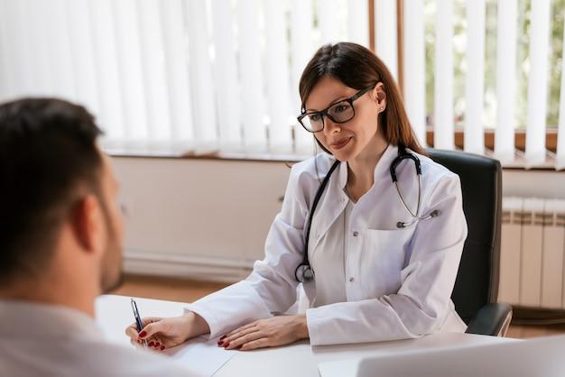 Ritratto di una bella dottoressa scrivendo una prescrizione medica per un paziente con un sorriso.
