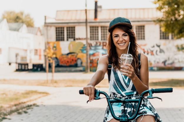 Ritratto di una bella giovane donna urbana con una bicicletta.