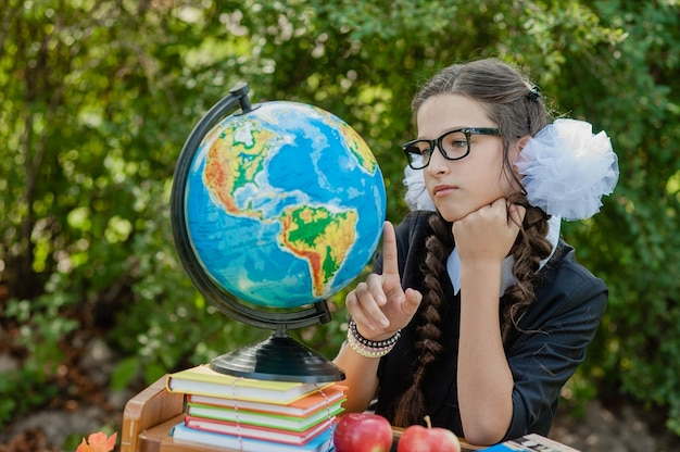 Ritratto di una bella giovane studentessa seduto a una scrivania