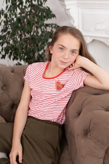 Ritratto di una bella ragazza adolescente rossa. ragazza carina seduta sul divano, sorridendo e guardando la telecamera