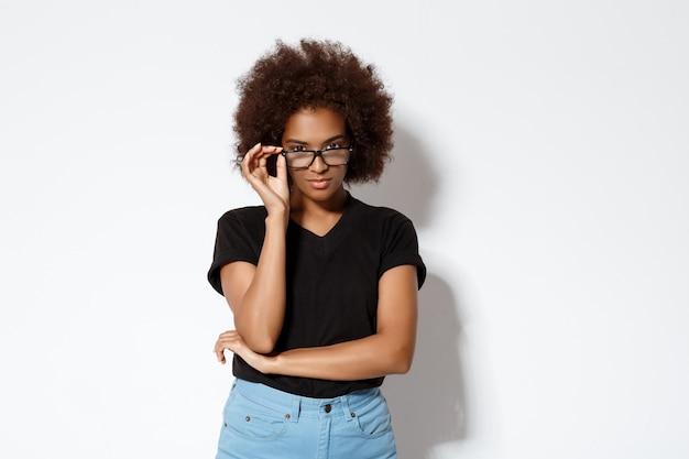 Ritratto di una bella ragazza africana con gli occhiali sul muro bianco