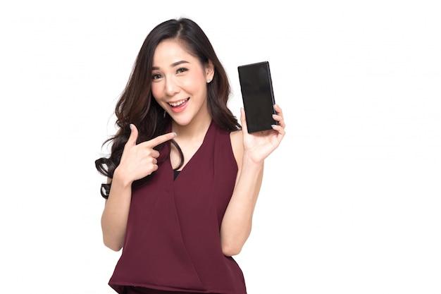 Ritratto di una bella ragazza allegra che indossa un abito rosso e che mostra o presenta l'applicazione del telefono cellulare e che punta il dito sullo smartphone a portata di mano
