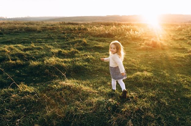 Ritratto di una bella ragazza bella e felice che attraversa il campo soleggiato