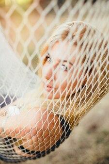 Ritratto di una bella ragazza bionda attraverso una rete amaca. ricreazione all'aperto.
