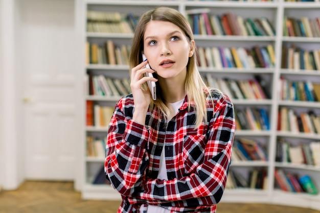 Ritratto di una bella ragazza bionda, che indossa abiti casual, parlando sul telefono cellulare, mentre in piedi in biblioteca davanti a diversi scaffali con libri