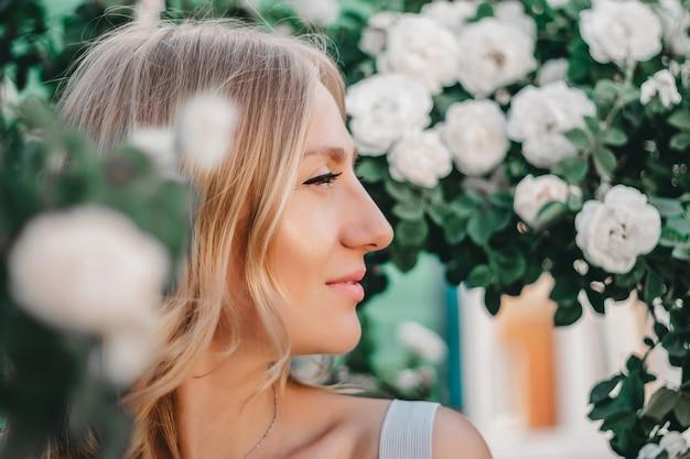 Ritratto di una bella ragazza bionda con acconciatura sullo sfondo di un cespuglio di rose bianche