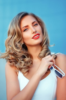 Ritratto di una bella ragazza bionda con occhiali da sole bianchi