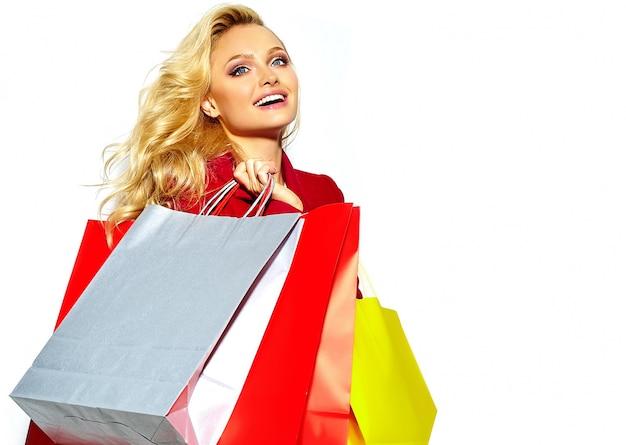 Ritratto di una bella ragazza bionda dolce sorridente felice carina che tiene nelle sue mani grandi borse colorate shopping in giacca rossa pantaloni a vita bassa isolato su bianco