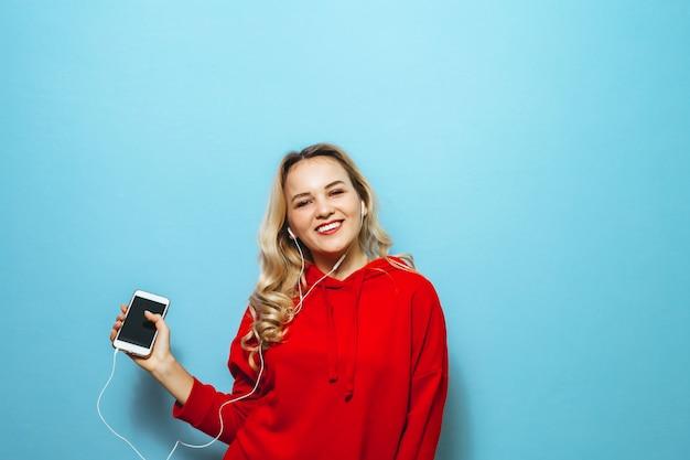 Ritratto di una bella ragazza bionda eccitata ascoltando musica in cuffia e ballando sul muro blu