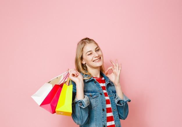 Ritratto di una bella ragazza bionda in possesso di borse per la spesa ed è felice su uno sfondo rosa
