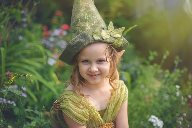 Ritratto di una bella ragazza carina in un cappello di gnomo e costume nella foresta verde.