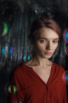Ritratto di una bella ragazza caucasica in camicia rossa. bolle di sapone volano intorno alla sua testa scintillante di colori arcobaleno.
