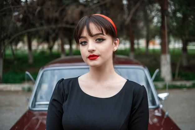 Ritratto di una bella ragazza caucasica in un abito vintage nero, in posa vicino a un auto d'epoca
