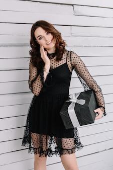 Ritratto di una bella ragazza che guarda con un regalo in una scatola
