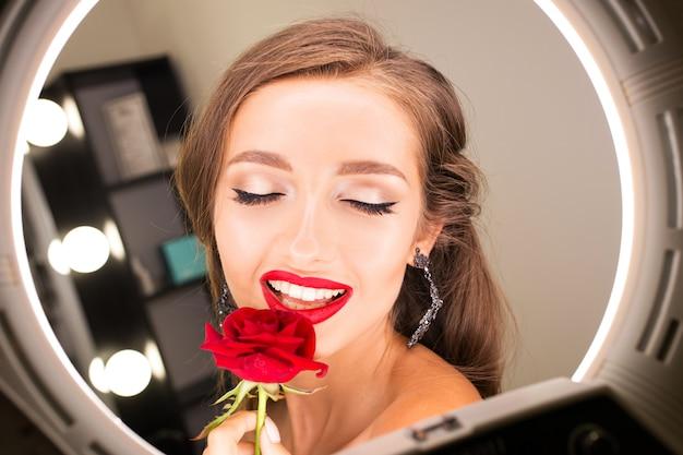 Ritratto di una bella ragazza con labbra rosse e una rosa