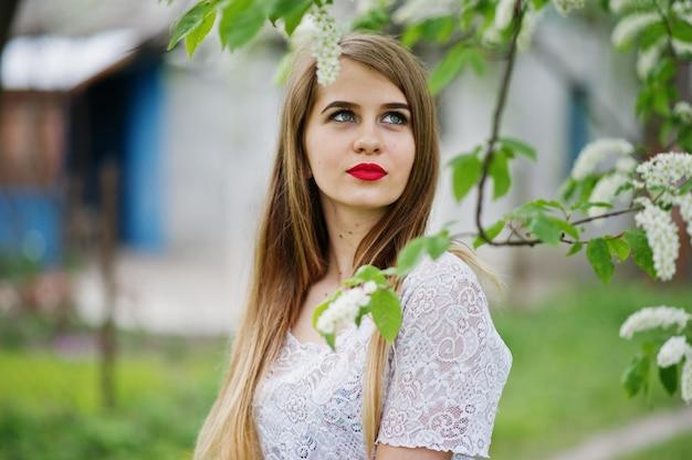 Ritratto di una bella ragazza con le labbra rosse al giardino di fiori di primavera, indossare abito rosso e camicetta bianca.