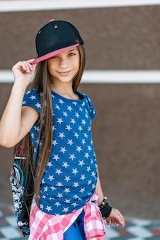 Ritratto di una bella ragazza con lunghi capelli sani in un cappello.