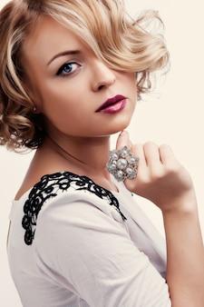 Ritratto di una bella ragazza con un anello di perle