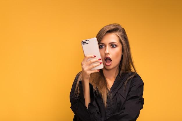 Ritratto di una bella ragazza con un telefono wooku su giallo