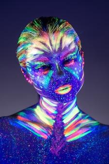 Ritratto di una bella ragazza con vernice ultravioletta sul viso.