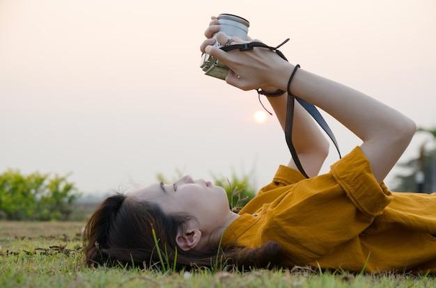 Ritratto di una bella ragazza, fare foto in estate parco verde con la macchina fotografica