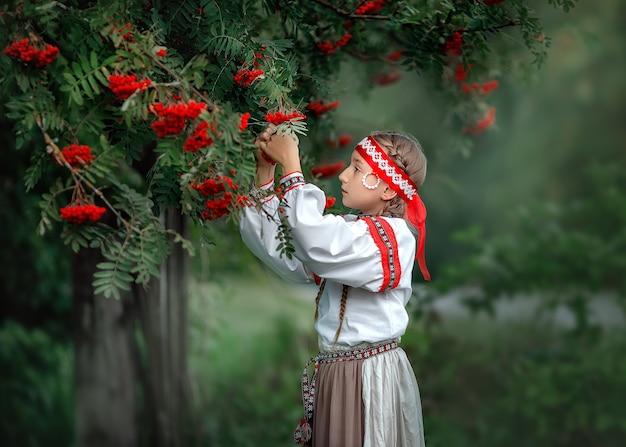 Ritratto di una bella ragazza in abito popolare vicino a un albero di sorbo