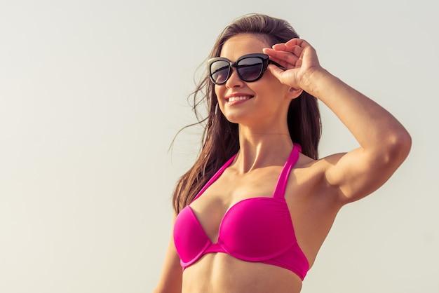 Ritratto di una bella ragazza in costume da bagno rosa e occhiali da sole.