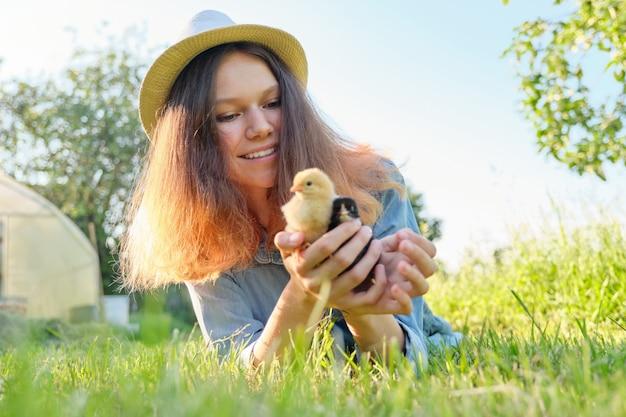 Ritratto di una bella ragazza in fattoria con due pulcini appena nati in mano