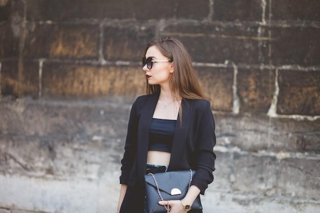 Ritratto di una bella ragazza in occhiali da sole e una borsa in mano su uno sfondo di un muro di pietra