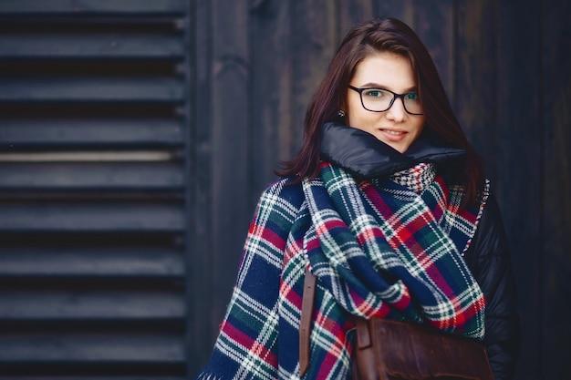 Ritratto di una bella ragazza in occhiali e una sciarpa contro un muro di legno