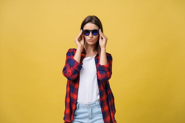 Ritratto di una bella ragazza in occhiali rotondi su uno sfondo giallo in studio.