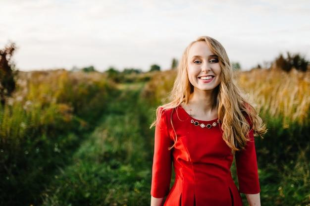Ritratto di una bella ragazza in piedi in autunno in un abito rosso contro il campo sulla natura. la metà superiore. guarda avanti. avvicinamento. capelli dissipati dal vento.