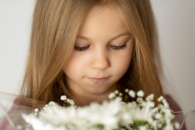 Ritratto di una bella ragazza in possesso di un mazzo di fiori bianchi