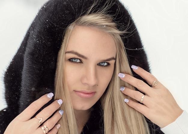 Ritratto di una bella ragazza in un cappotto invernale e un cappuccio in testa.