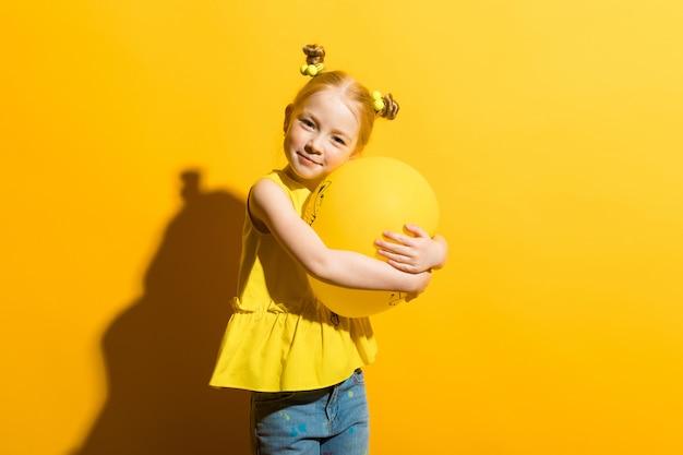 Ritratto di una bella ragazza in una camicia gialla e blue jeans.